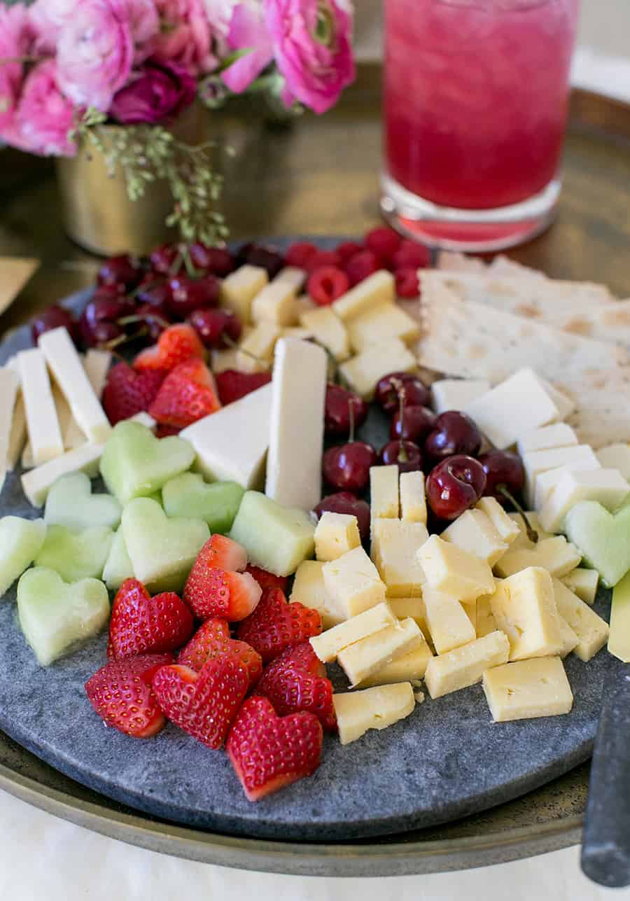 Valentine's Day Cheese platter with cheese and heart shaped fruit.