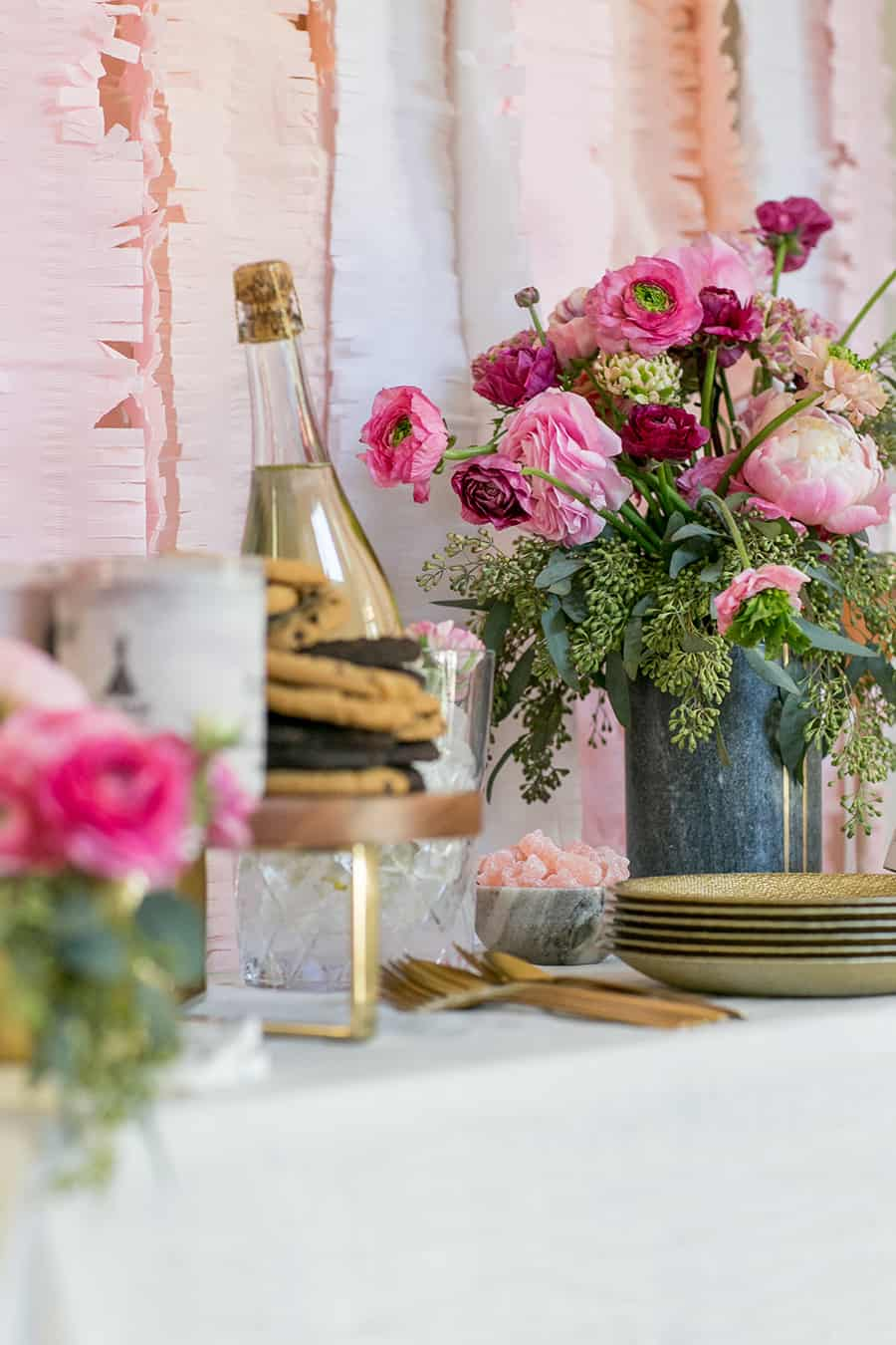 Valentine's Day bar with flowers, cookies, plates and sparkling wine.