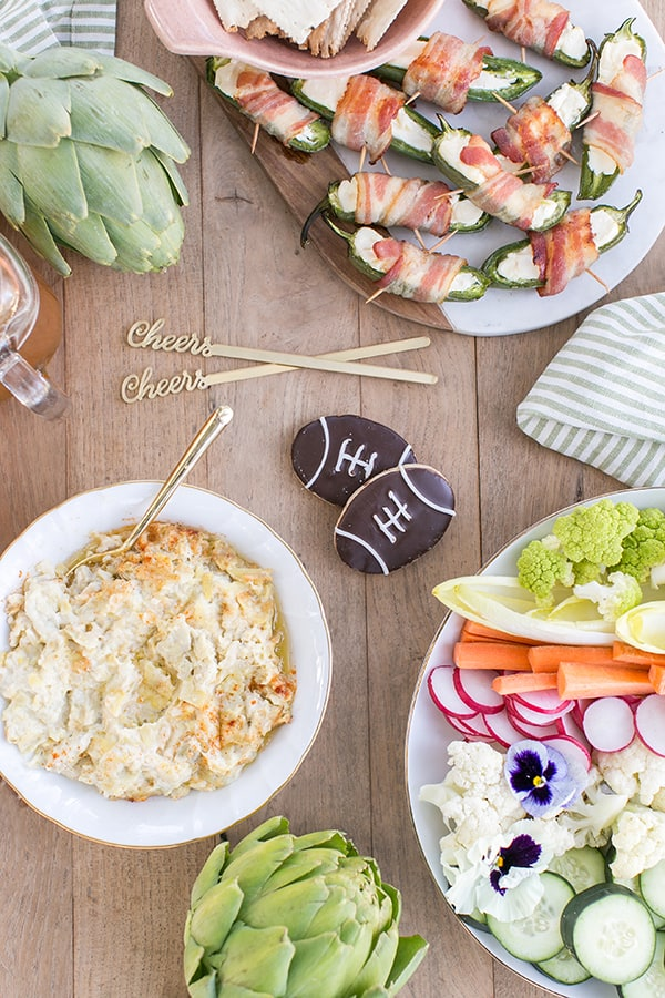 game day food, artichoke dip, football cookies and colorful vegetables
