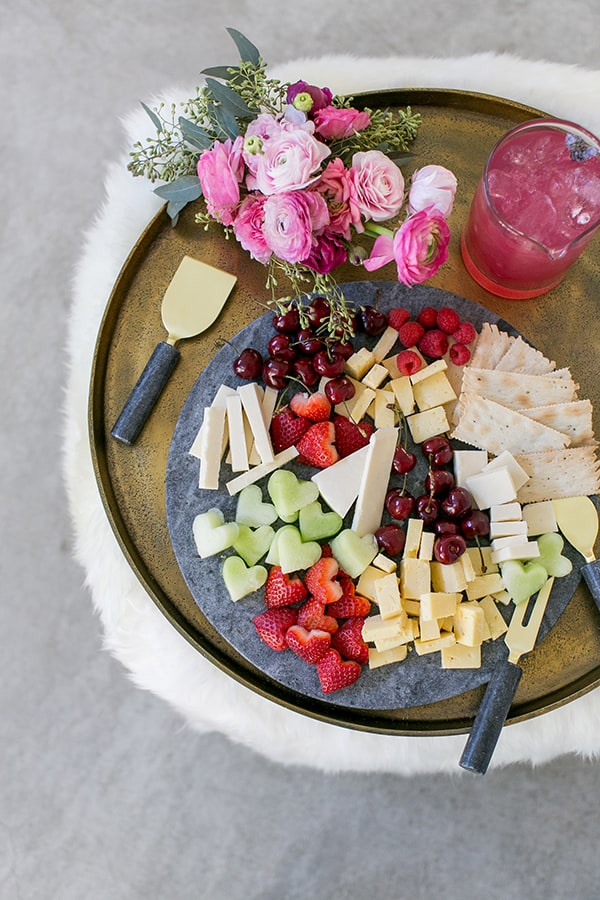 A cheese plate with heart shaped fruit and cheese on a marble board.