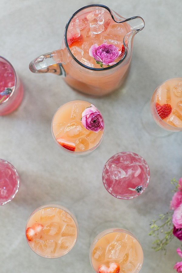 A rosé spritzer with edible flowers in a pitcher for a Valentine's Day party