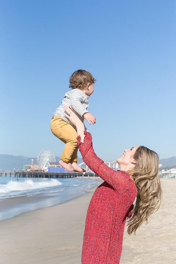 Eden Passante holds baby in Santa Monica on the beach.