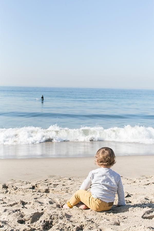 Baby watching a surfer on the beach in Santa Monica