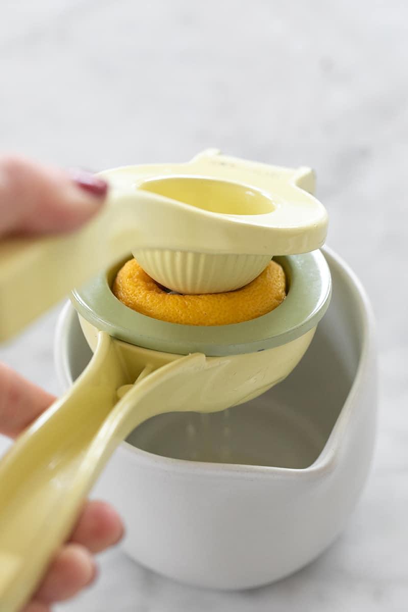 Squeezing fresh lemon into a bowl.