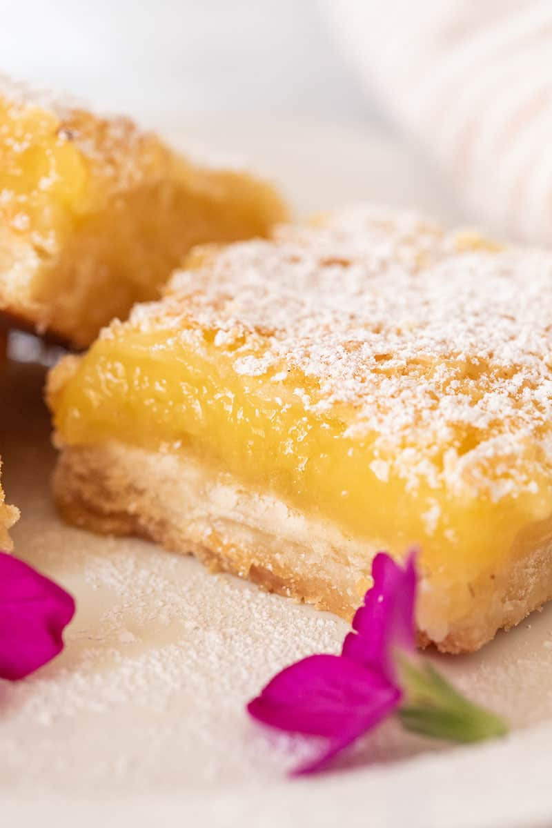 Close up picture of a lemon bar with powdered sugar and edible pink flowers.