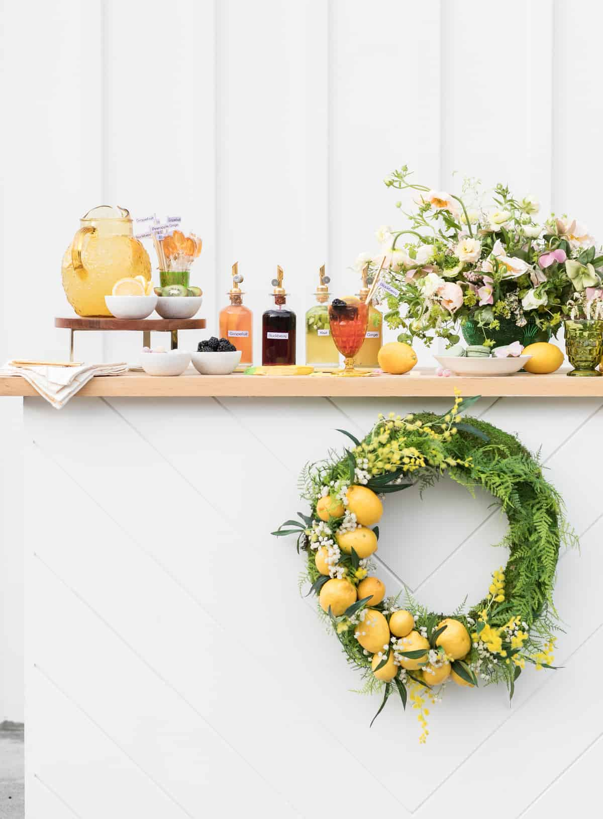 white lemonade stand with homemade syrups, lemon wreath, flowers.