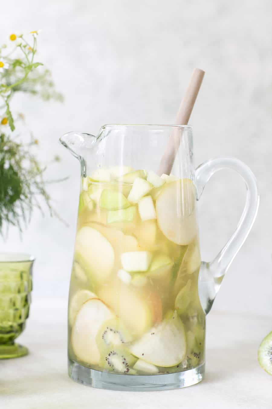 Green Irish Whiskey Sangria in a tall pitcher with sliced green fruit.