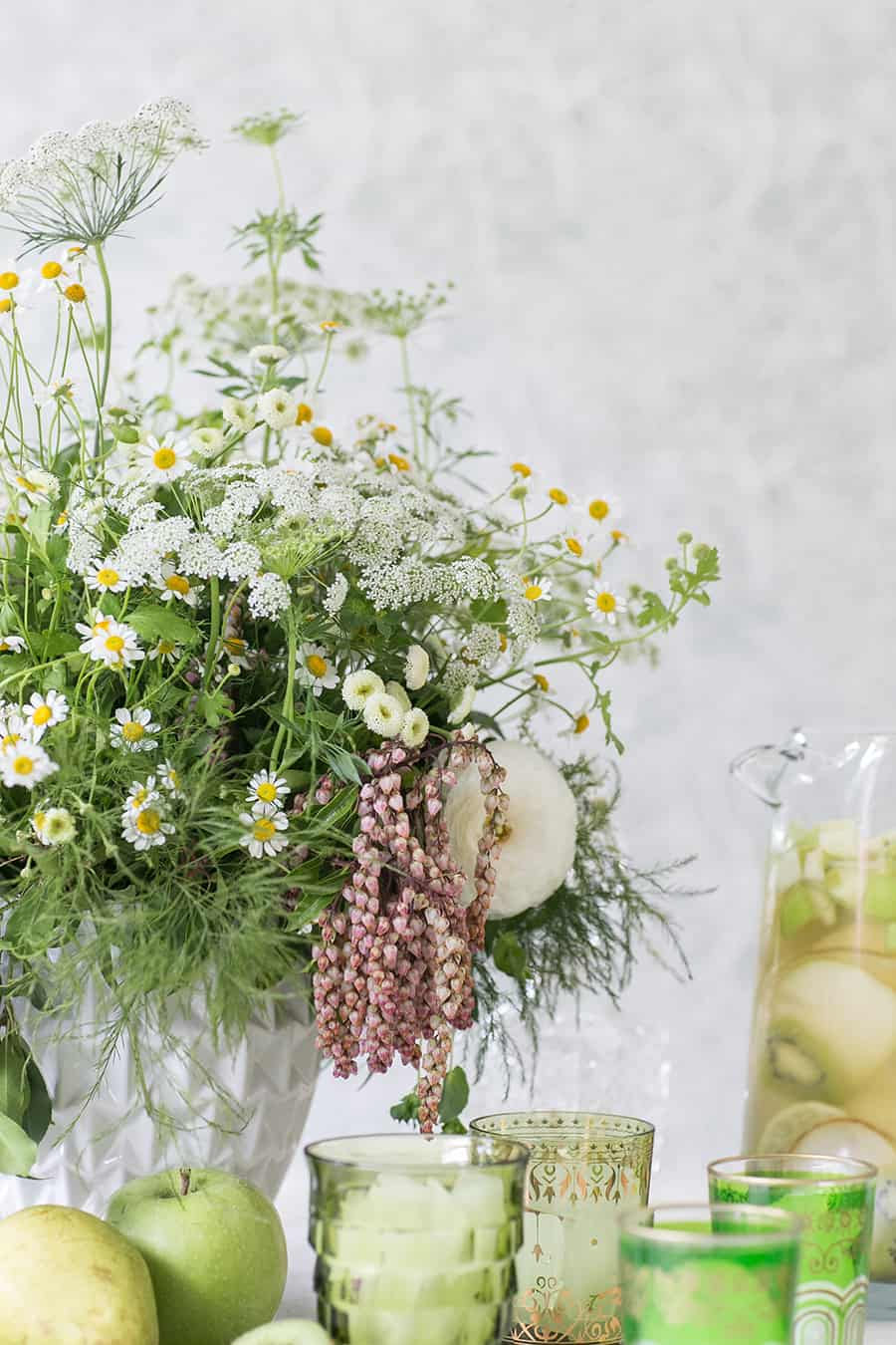 Flowers and green glasses filled with Green Irish Whiskey Sangria