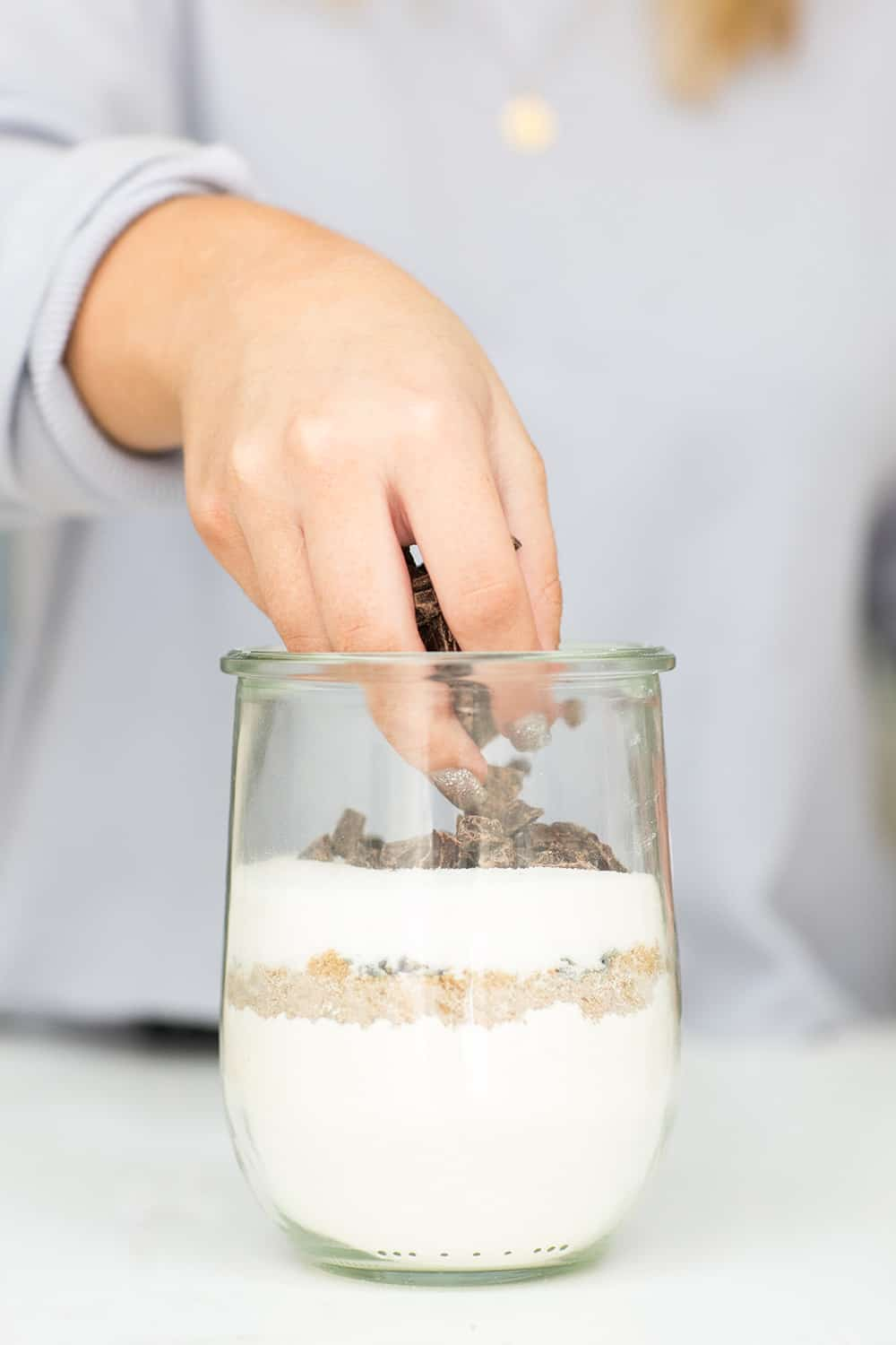 layering chocolate on top layer in jar, creating cookie mix in a jar