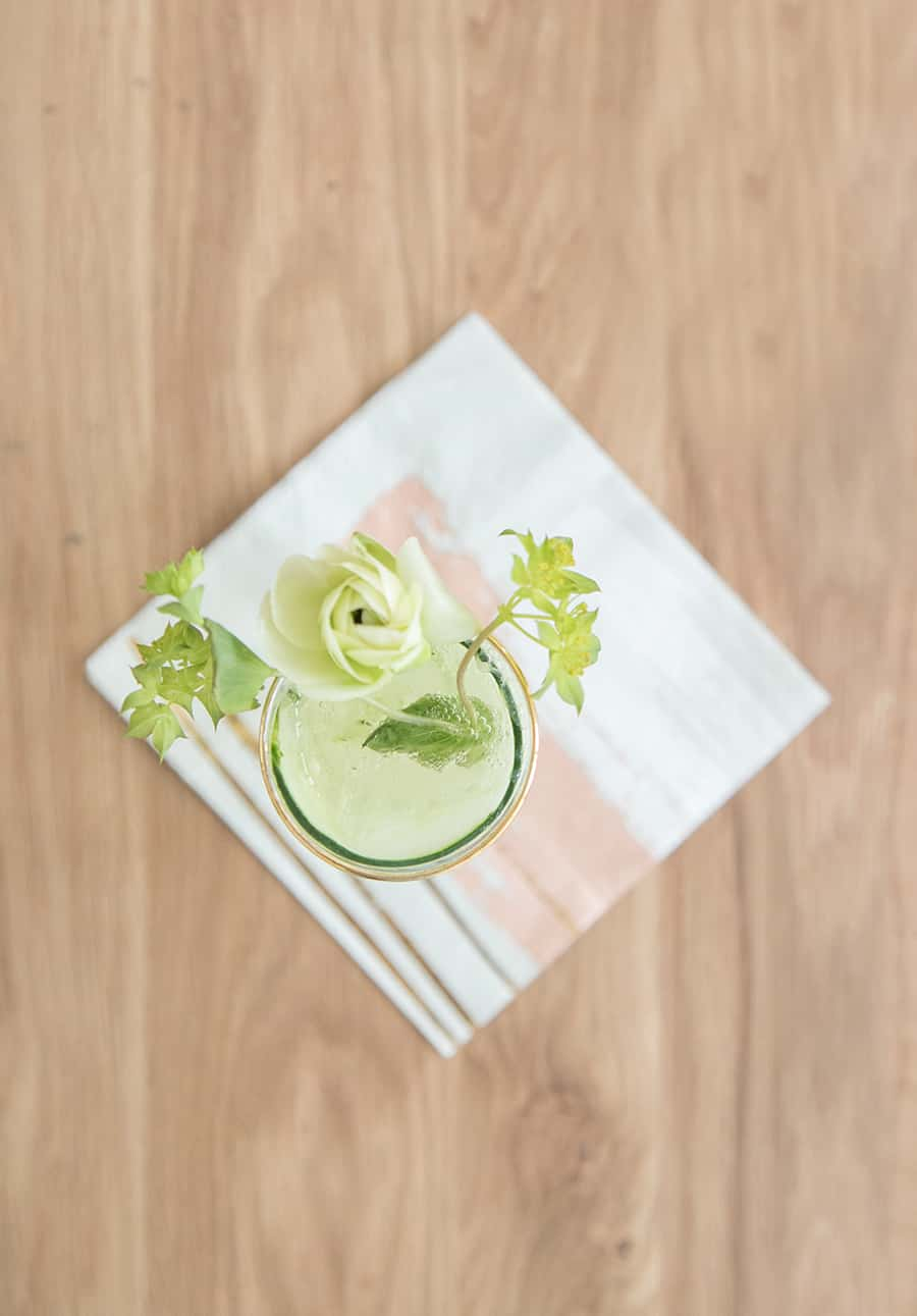 Cucumber and Kiwi Gimlet on a wooden table with flowers and a napkin.