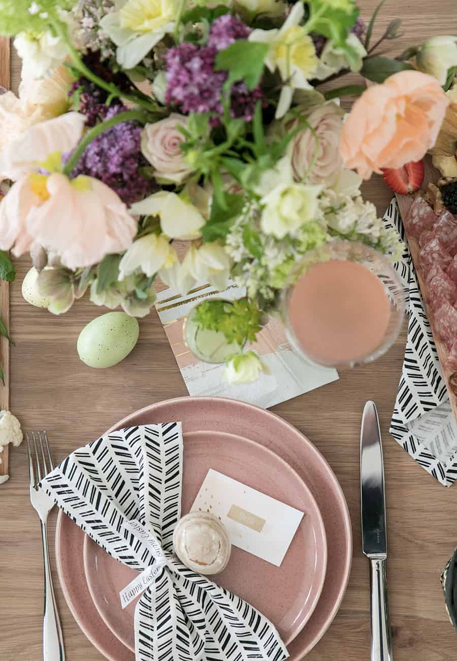 Easter table setting with pink plates with black napkin and easter egg.