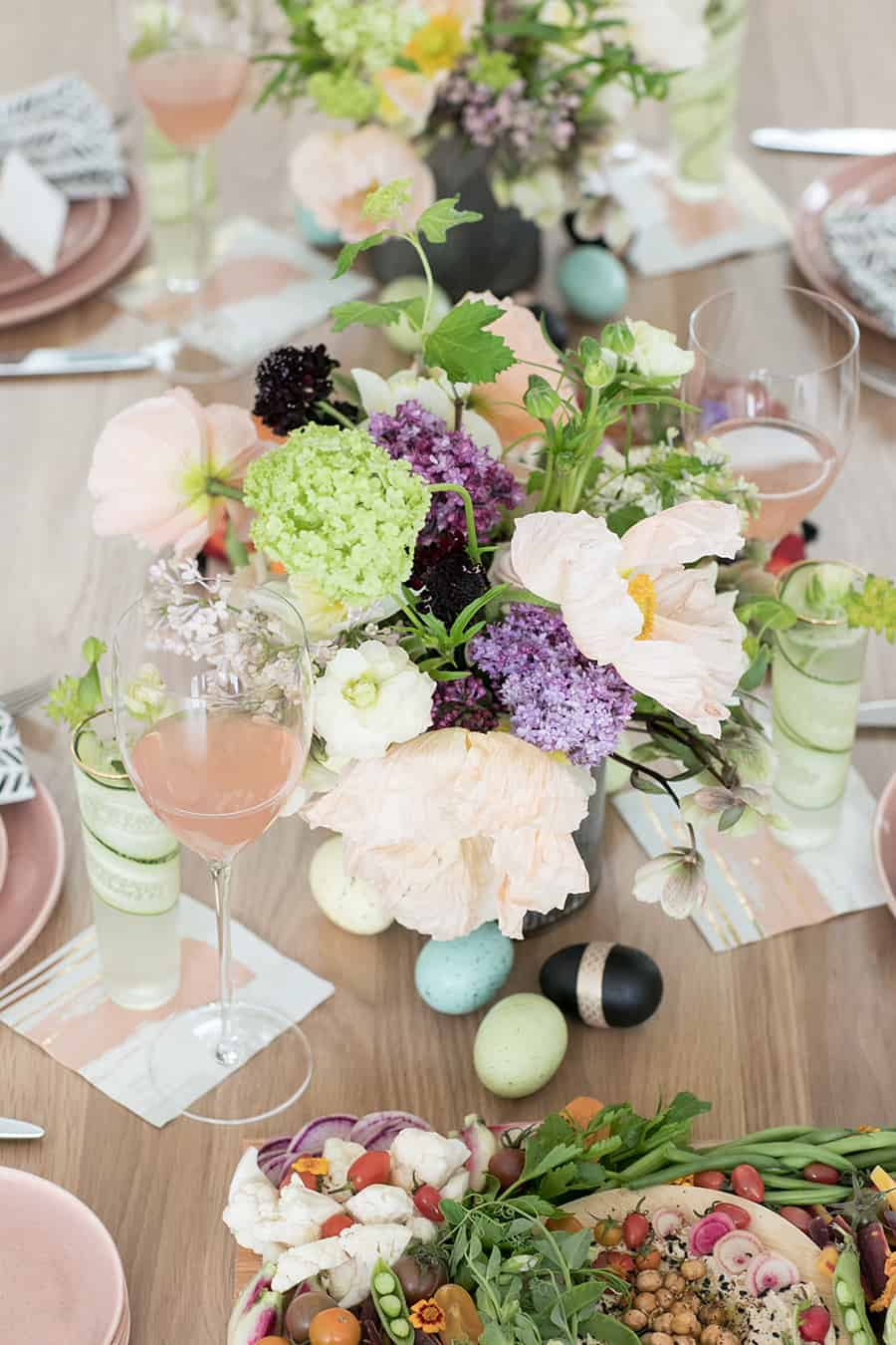 Easter brunch flowers on a table with a glass of rose and Easter eggs.