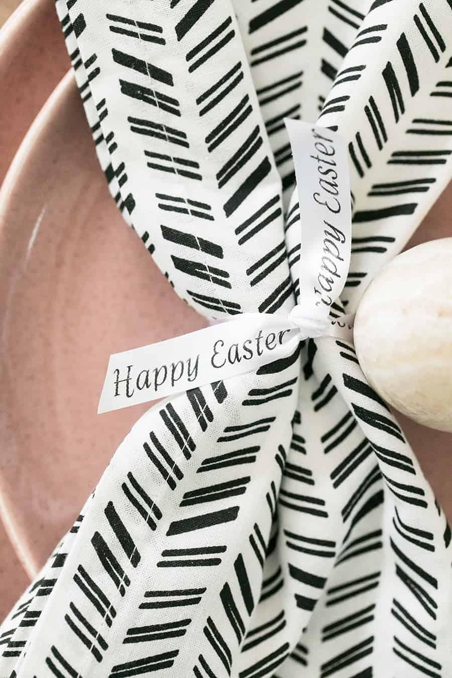 "Black and white napkin with custom ""happy Easter"" ribbon tied around the napkin."