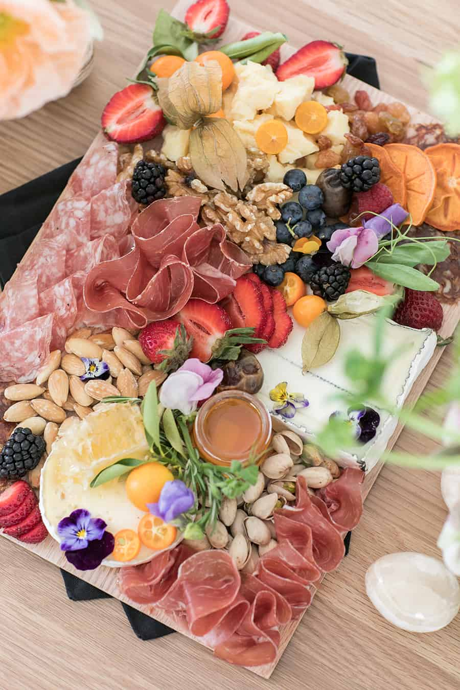 Charcuterie platter with fruit, cheese, nuts, almonds, meat and strawberries