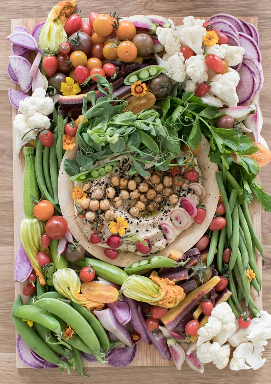 Vegetable platter with hummus and colorful vegetables.