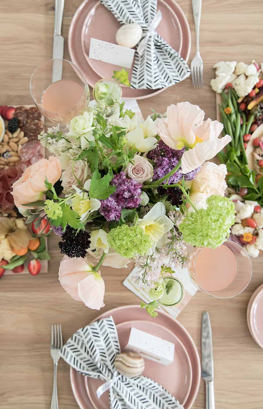 Overhead of flowers on a table with pink plates and Easter eggs.