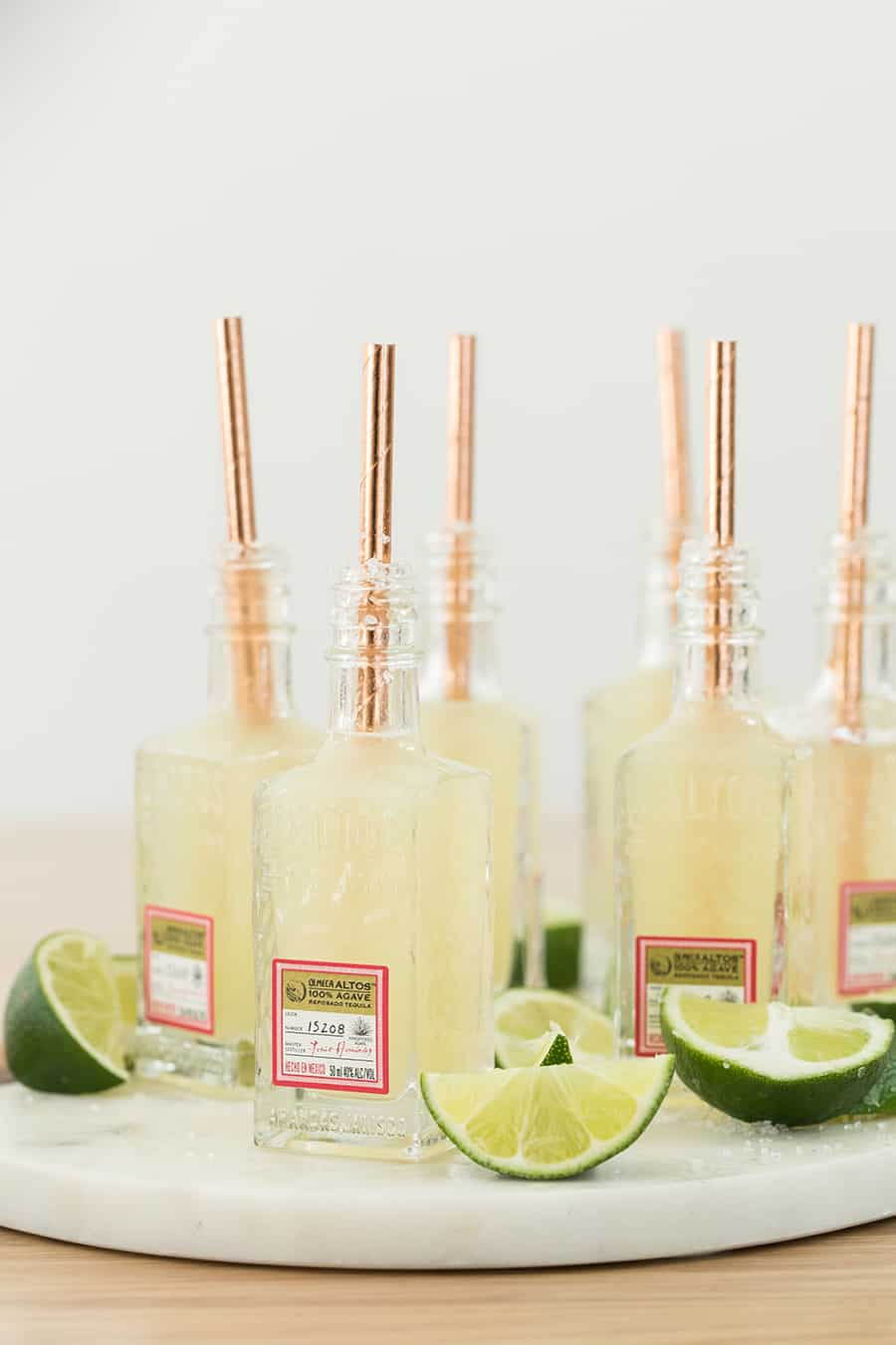 Mini margaritas served in tiny tequila bottles with a lime wedge and copper straw.