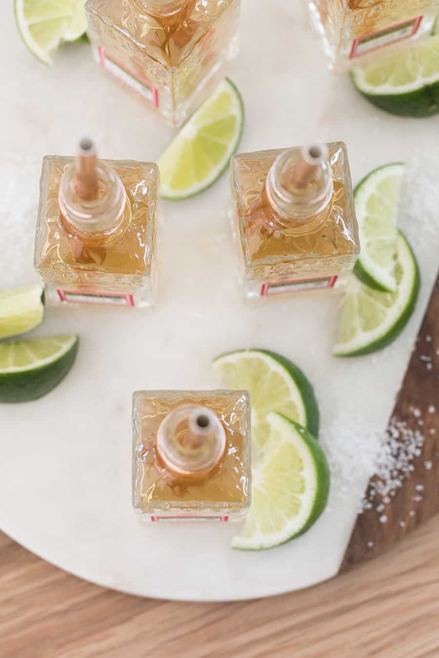 Mini tequila shots on marble platter with lime wedges and salt.