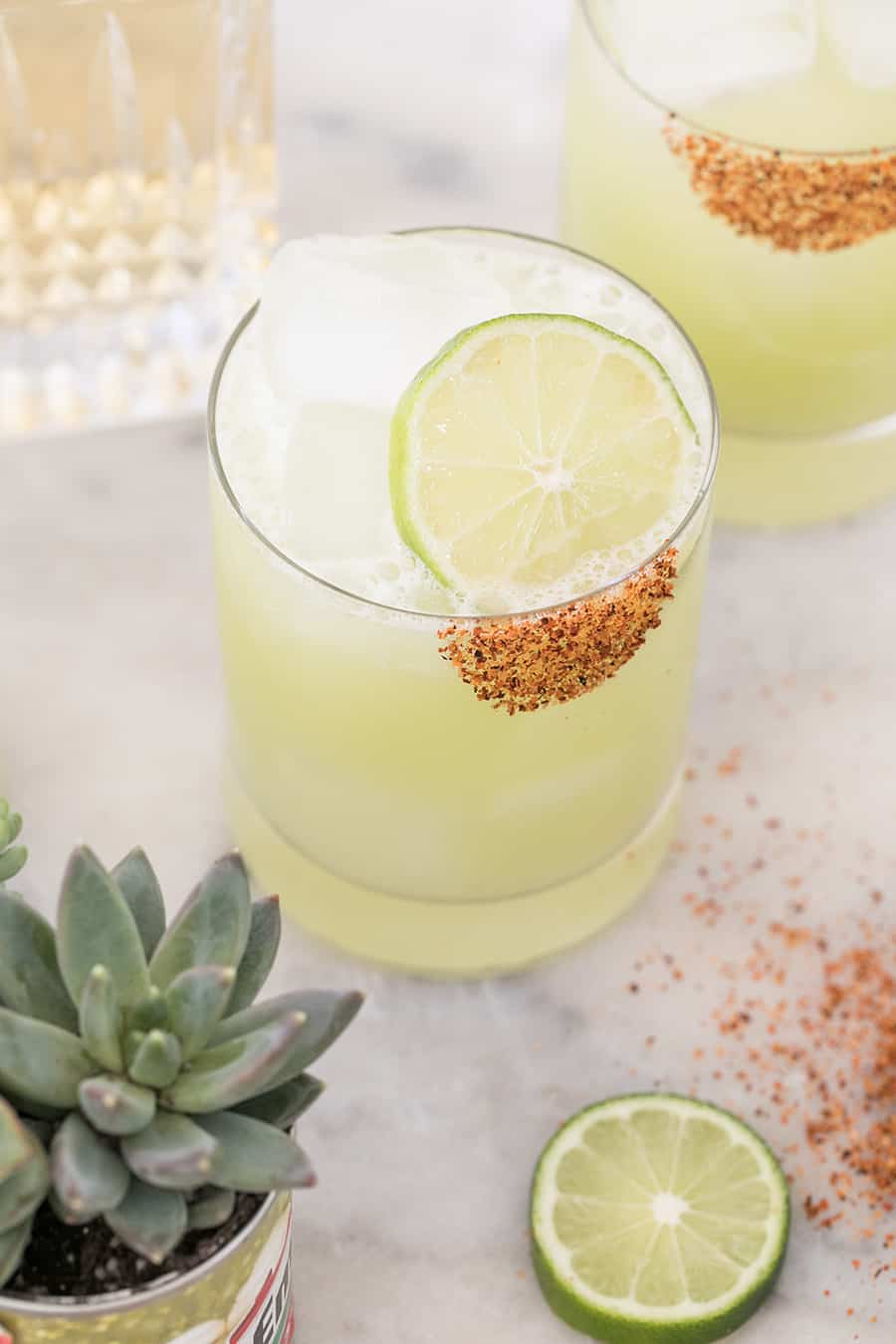 Honeydew margarita with lime slice and chili salt.