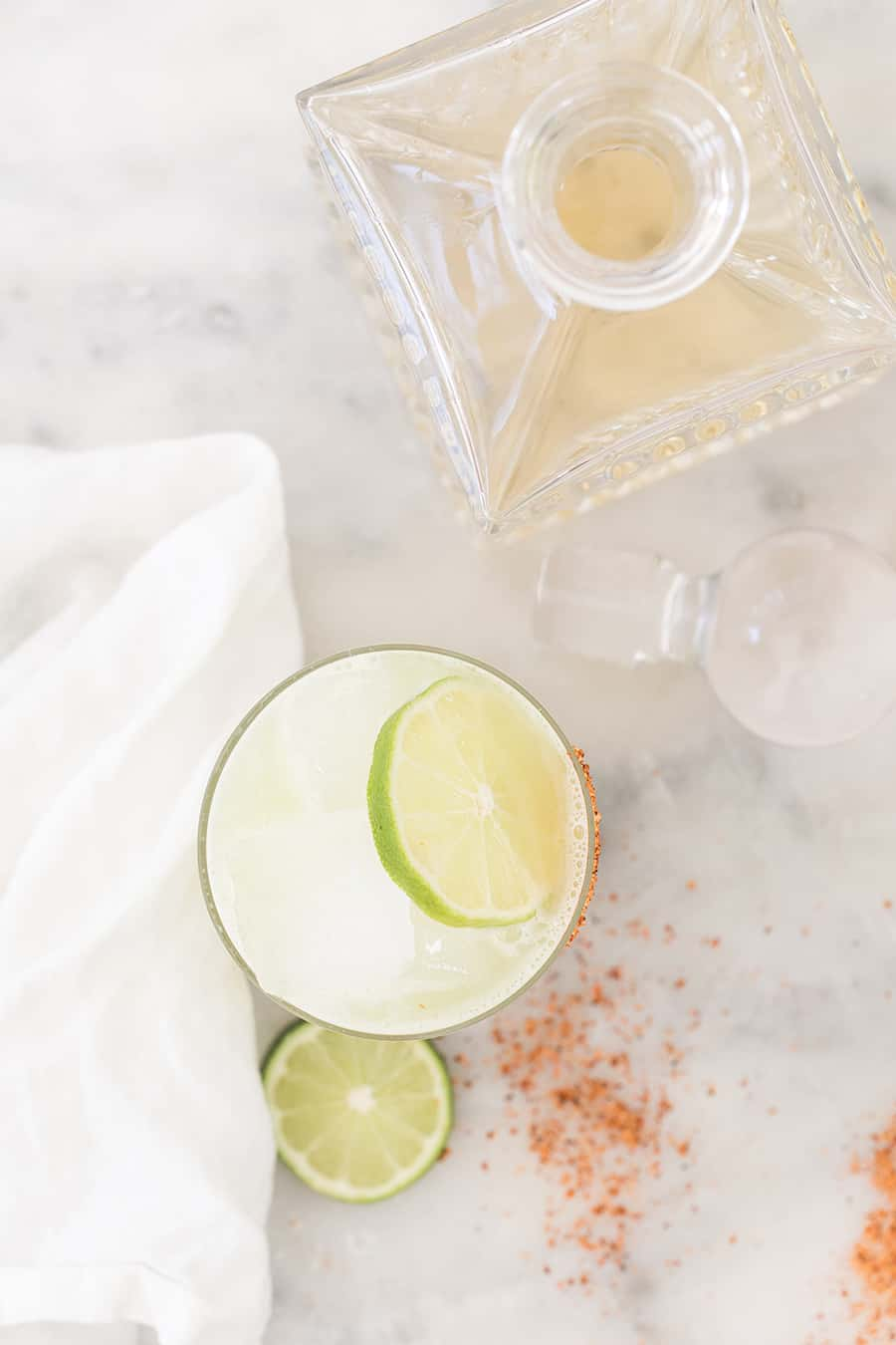 Cocktail with lime wedge and a bottle of tequila.