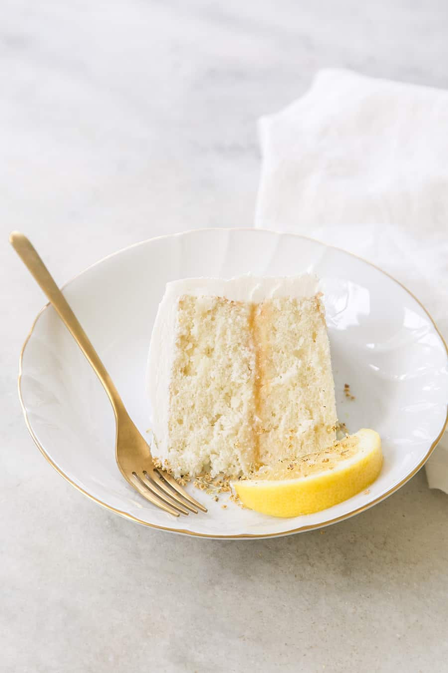 A slice of lemon elderflower cake on a white plate