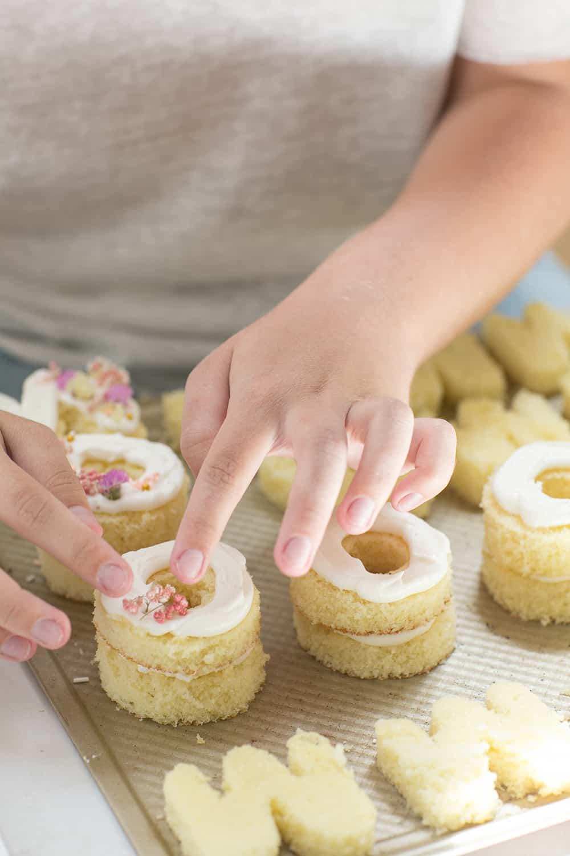 pressing flowers onto mini cakes