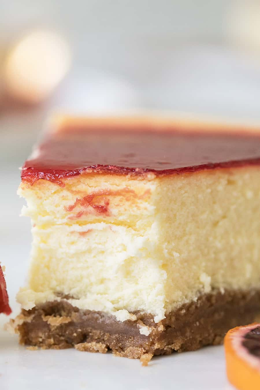 Slice of cheesecake with blood orange sauce.