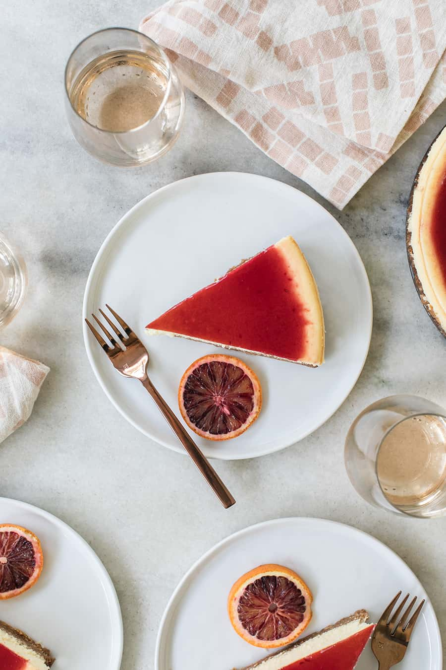 blood orange cheesecake on a white plate with a gold fork and slice of orange.