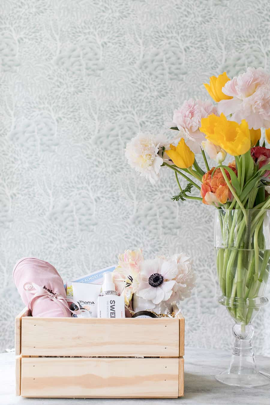 Baby gift basket in a wooden crate with flowers.