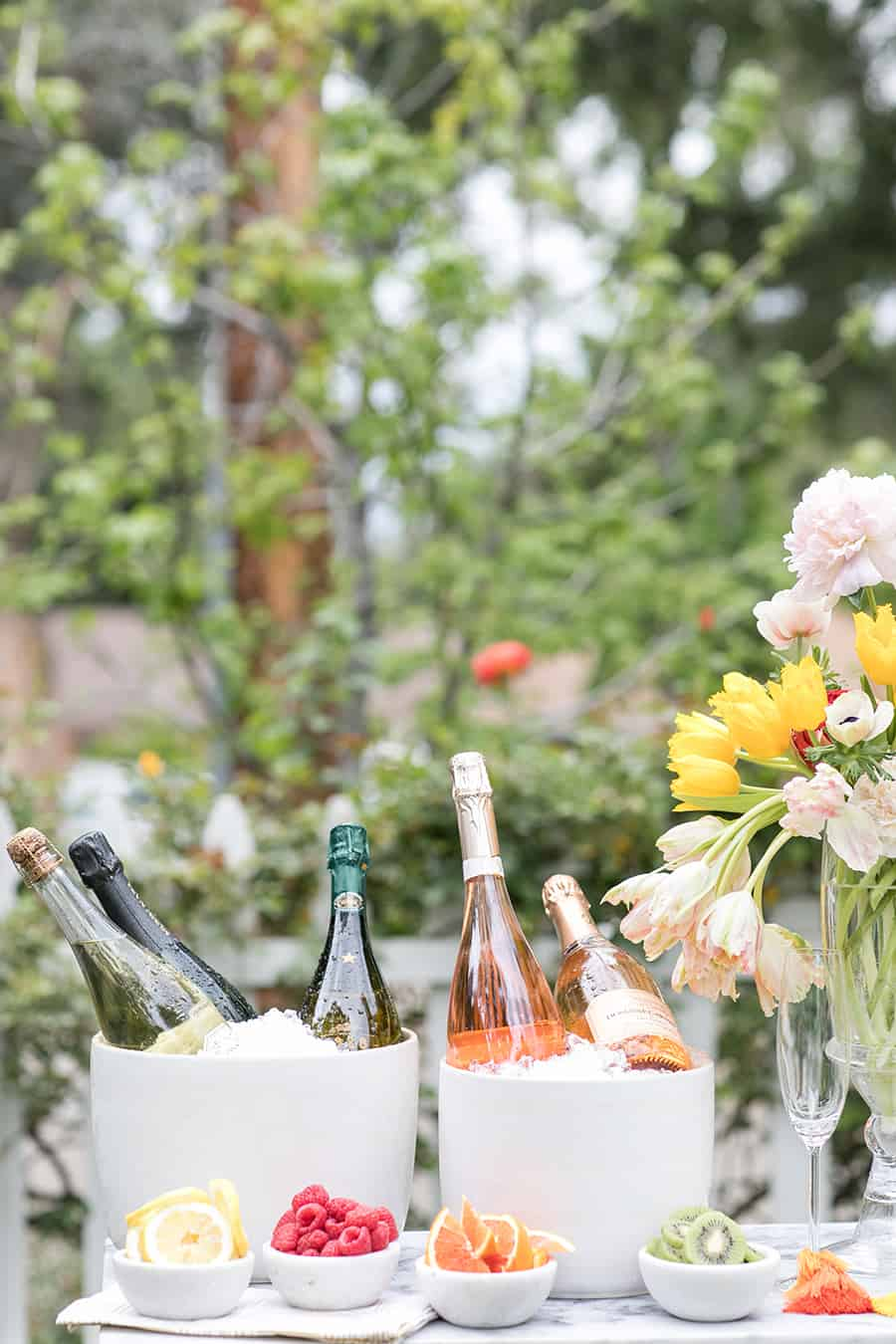 Bottles of Champagne over ice with bowls of fruit.