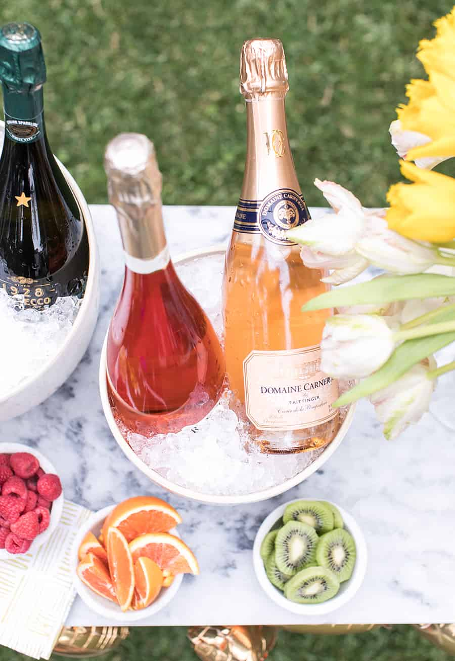 four bottles of champagne over ice with small bowls of fruit.