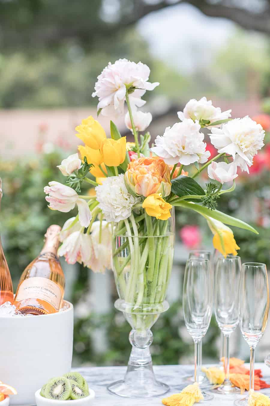 Beautiful flowers in a tall vase with champagne glasses and tassels.