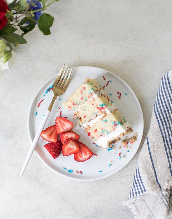 slice of funfetti dessert on a plate with strawberries