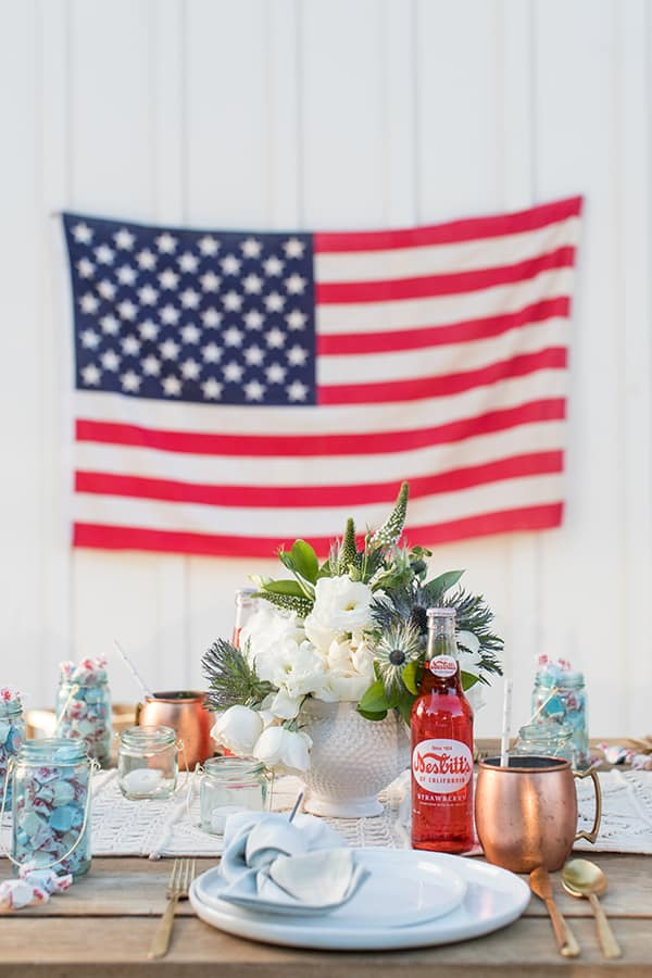 4th of July party with an American flag, vase of flowers, copper mugs, red sodas.