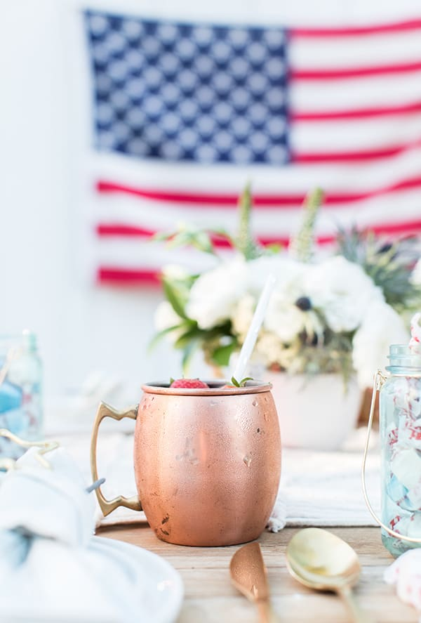 Blueberry Moscow Mule in a copper mug on a 4th of July table setting.