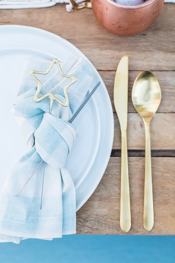 Blue and white napkin, gold flatware with sparkles.