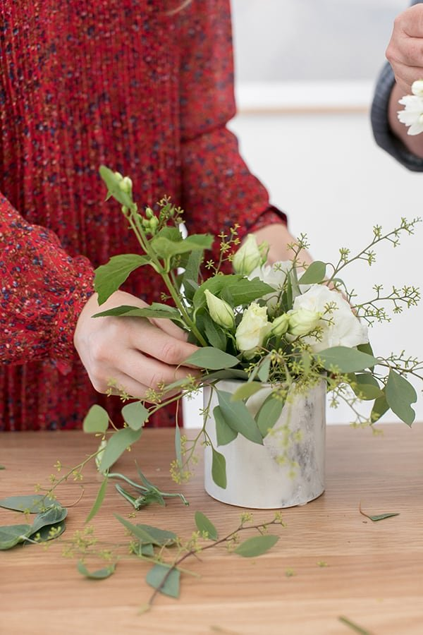 Arranging flowers in a marble vase.
