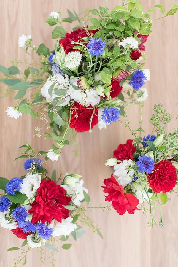 4th of July flowers, red, white and blue on a wood table.