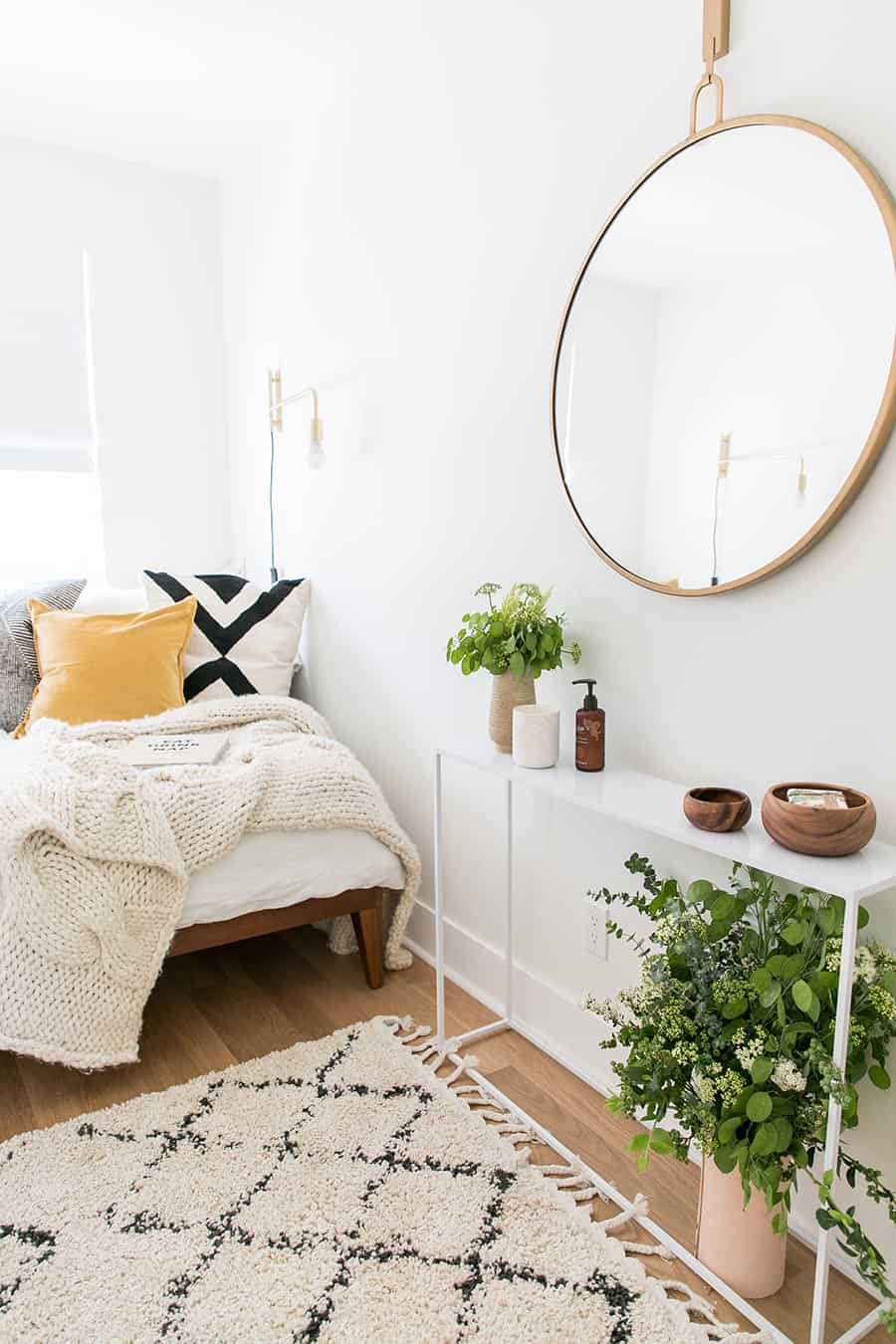A guest bedroom retreat with rug, mirror, flowers, bed, pillows.