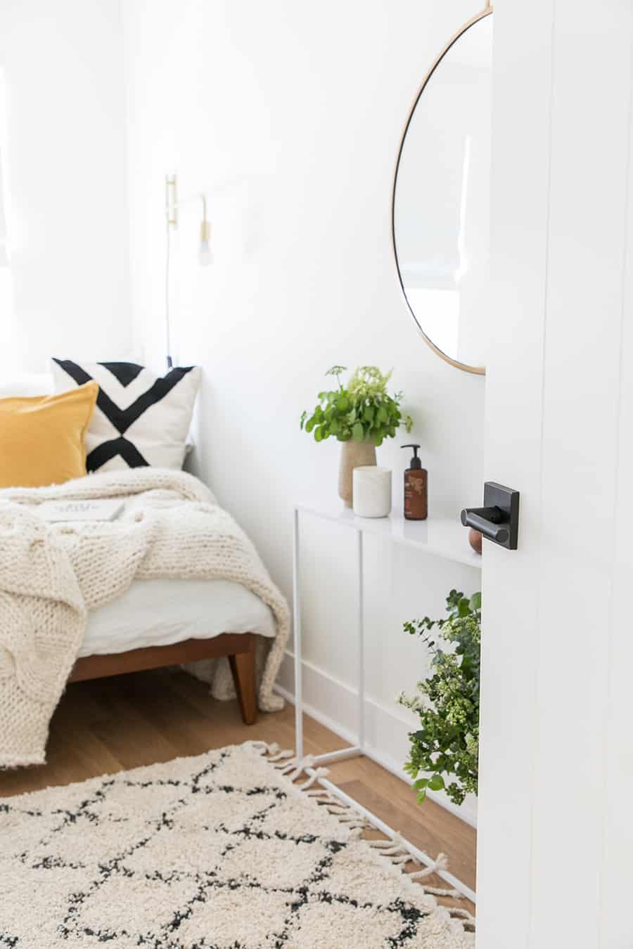 Door open to a guest bedroom with a bed, mirror and pillows.