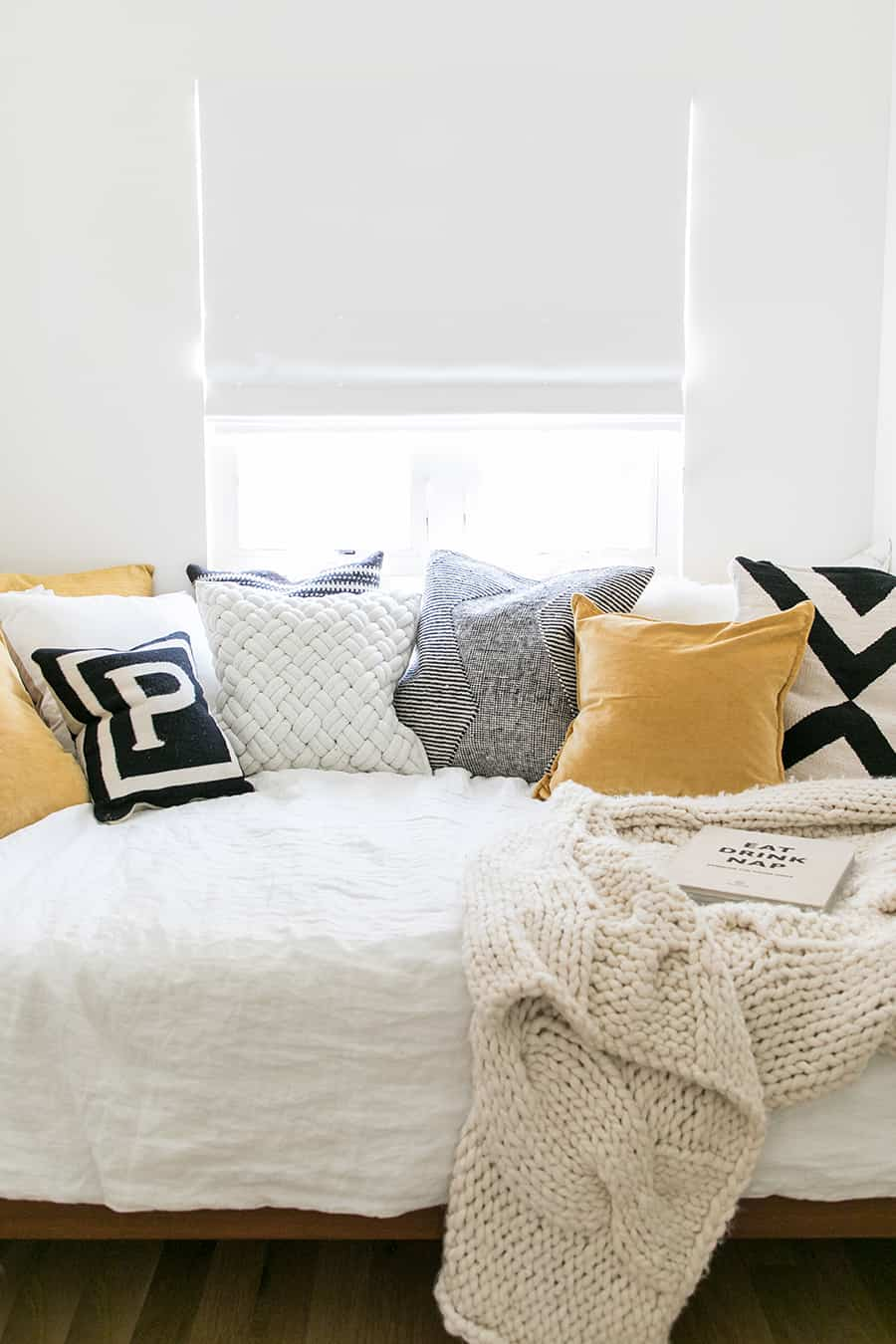 A bed with pillows and a knit blanket
