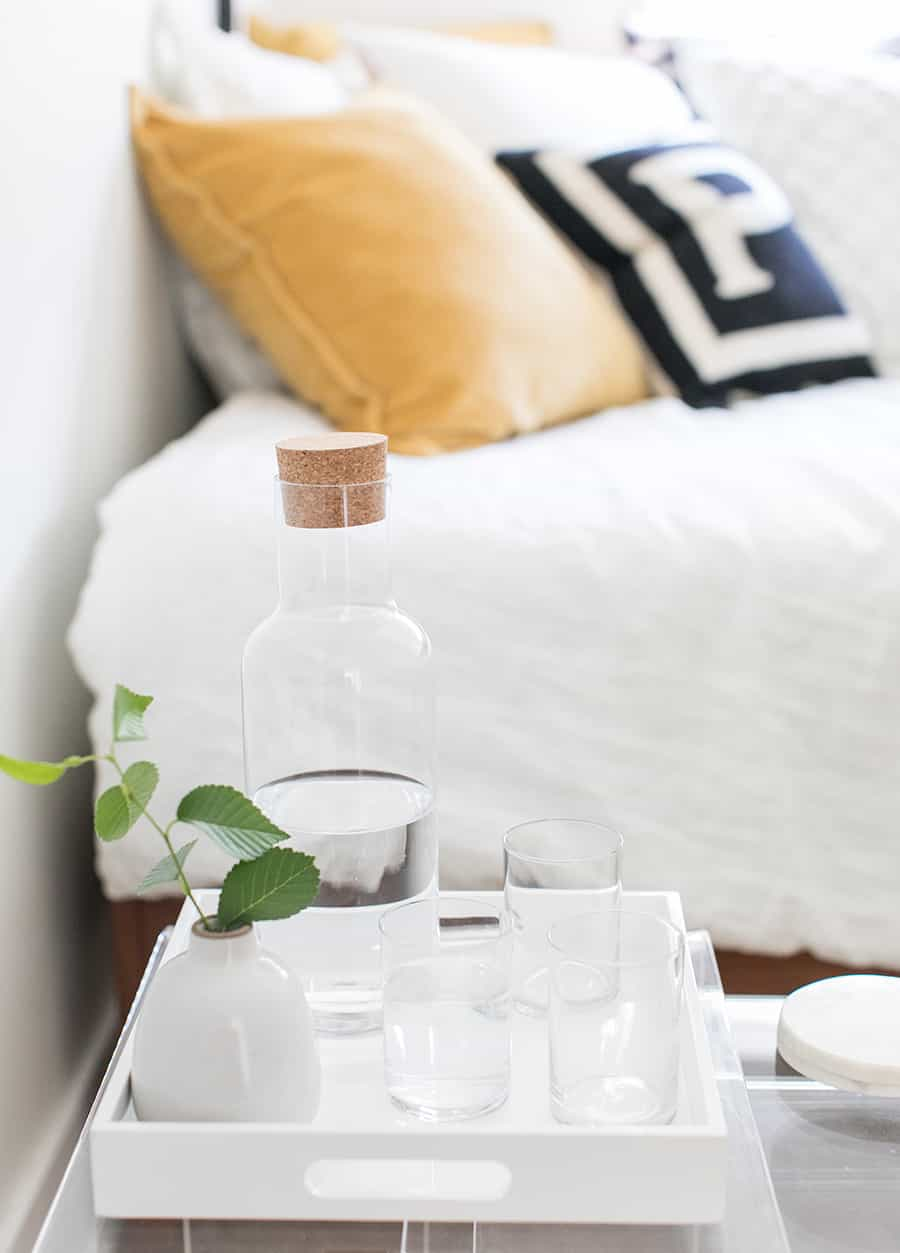 Water and cups next to a bed.