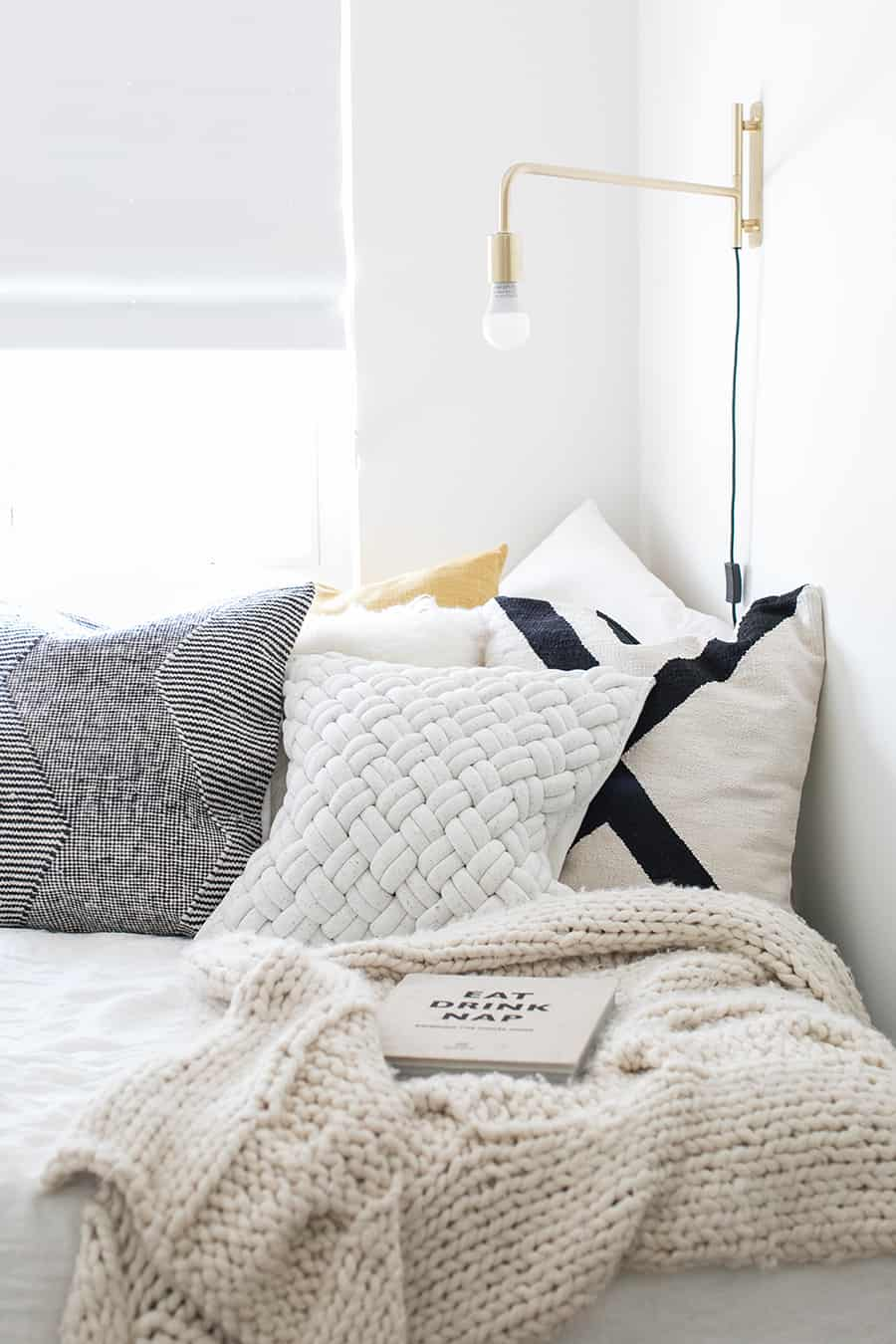 Pillows on a bed with a swing lamp and a knit blanket.