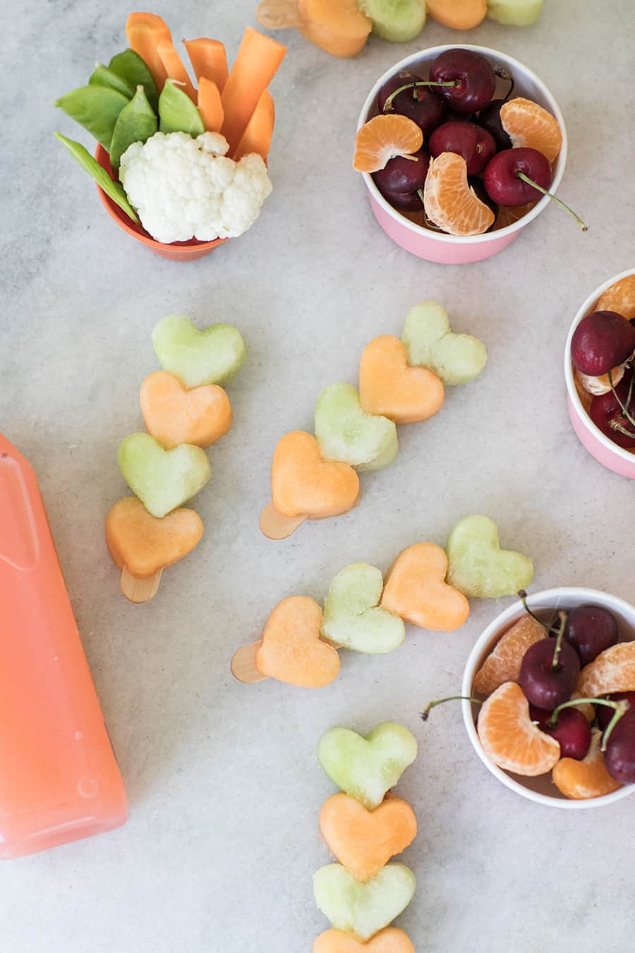 Heart fruit kabobs on a popsicle stick with a bowl of cherries and orange slices.