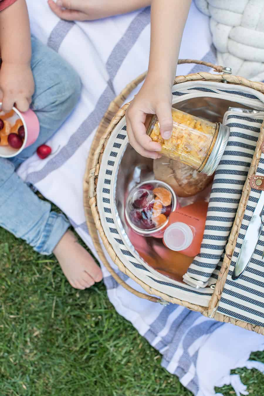 Food for kids in a picnic basket with a kids hand grabbing mac and cheese in a glass jar.