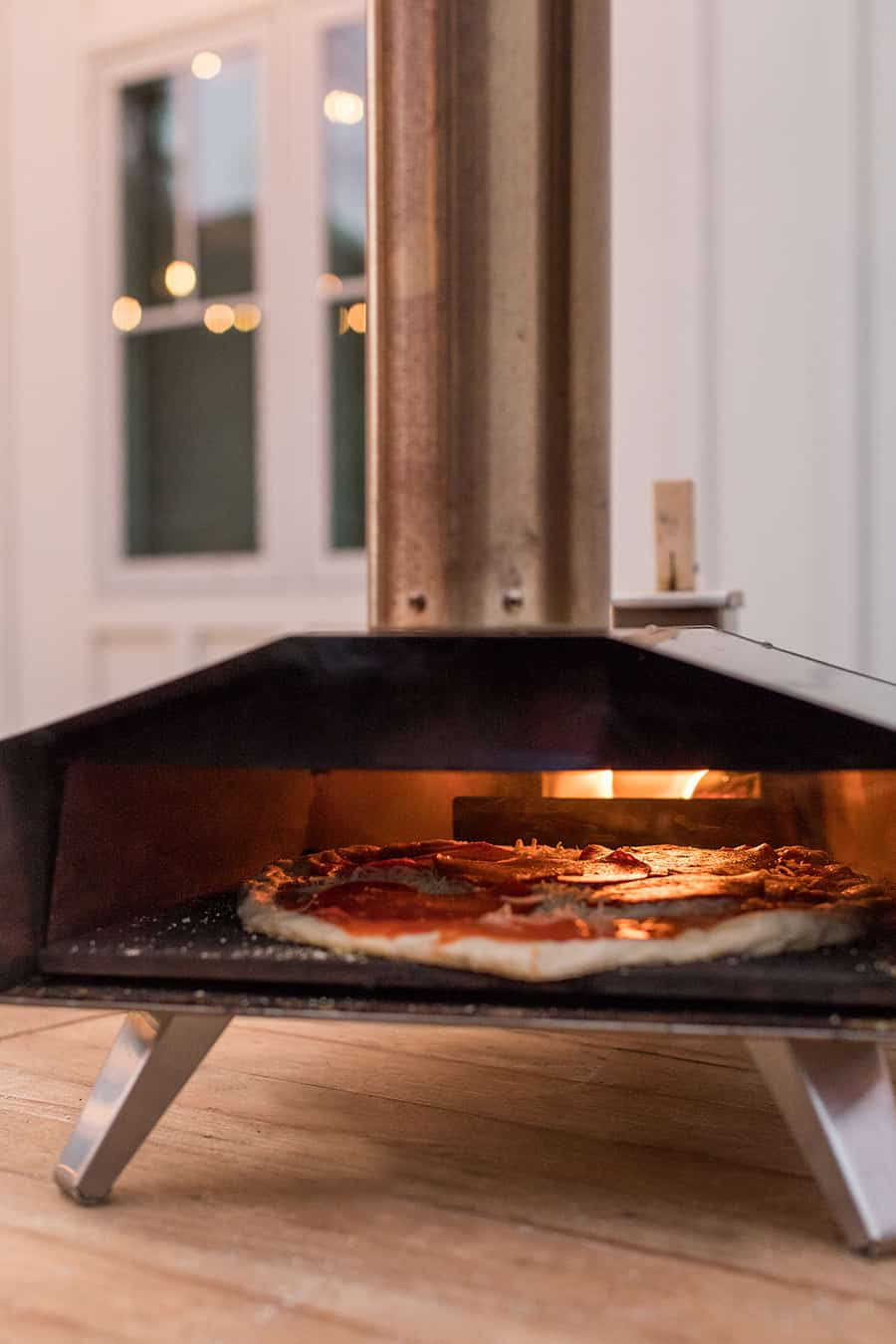 Uuni pizza oven with pizza cooking inside.