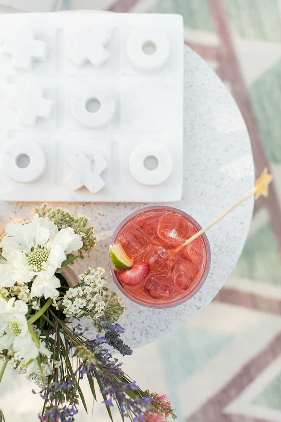 red cocktail on a table with flowers and a tic-tac-toe board.