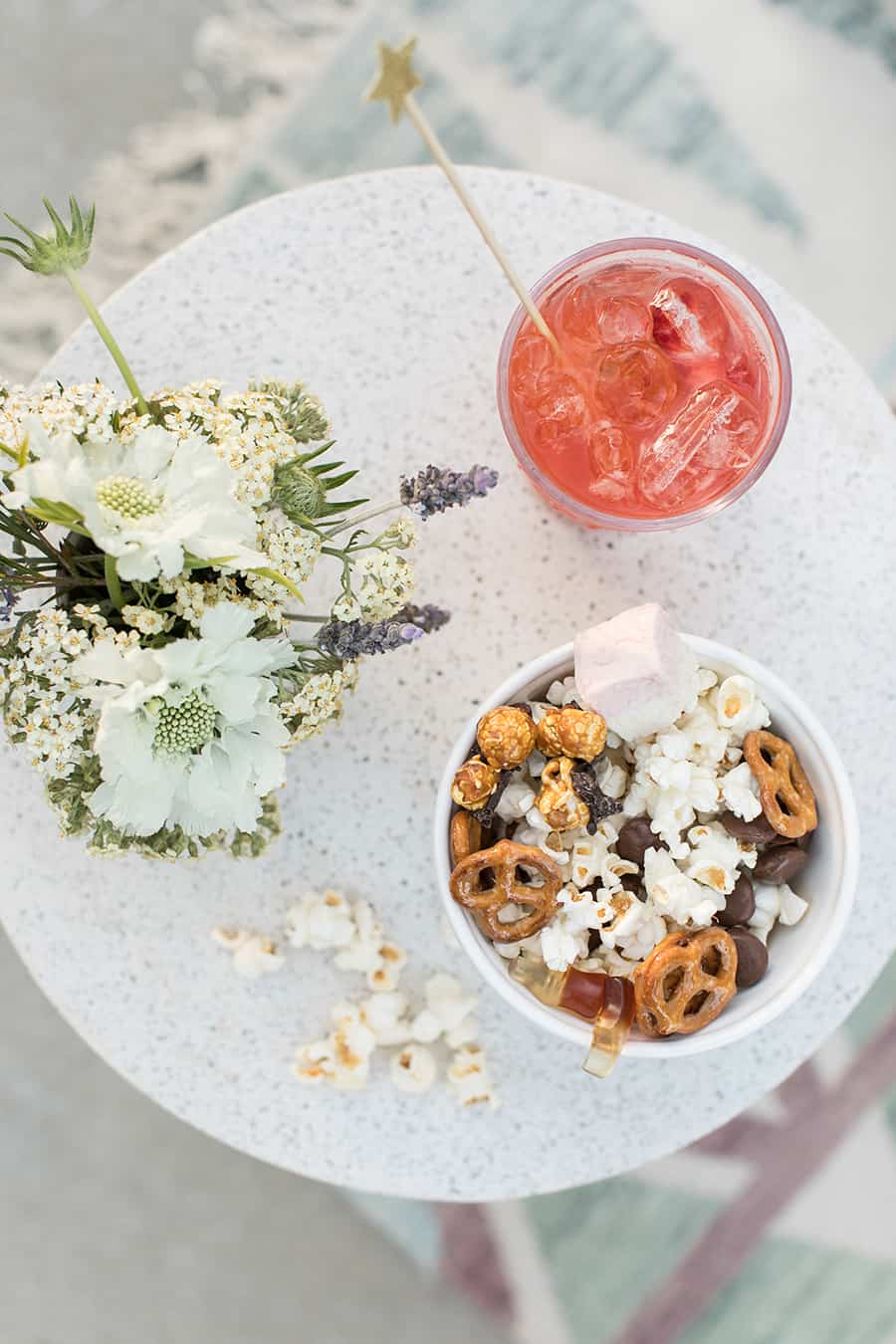 overhead photo of red cocktail and a bowl of popcorn with flowers on an outdoor table.