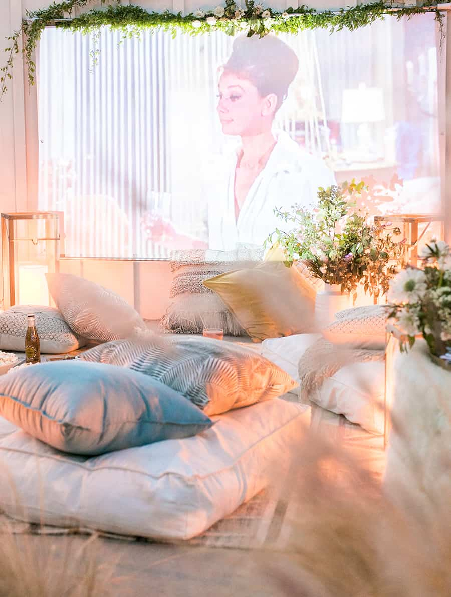 Outdoor movie screen with pillows, lights and flowers