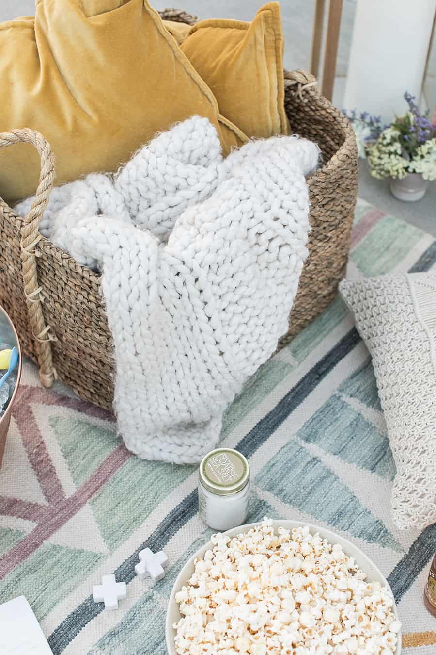 Basket with knitted blanket, bowl of popcorn on a modern blue rug.